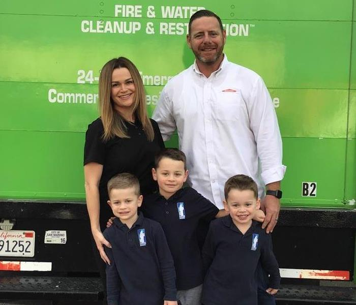 Family standing in front of green truck