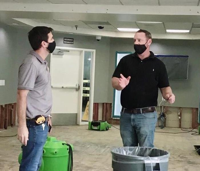 Two men talking in a commercial building